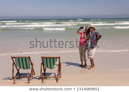Front view of senior couple taking selfie with mobile phone on beach in the sunshine Stock photo © wavebreak_media