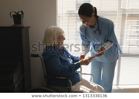 Female doctor discussing medical report with disable senior woman on digital tablet at home Stock photo © wavebreak_media