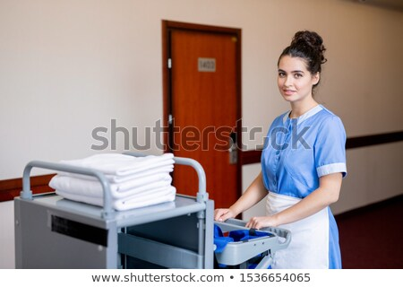 Chamber maid pulling cart with clean towels while moving along corridor in hotel Stock photo © pressmaster