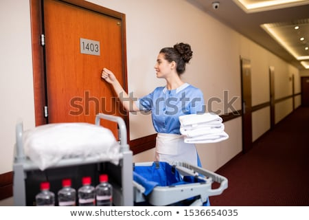 Young contemporary chamber maid with towels knocking on one of wooden doors Stock photo © pressmaster