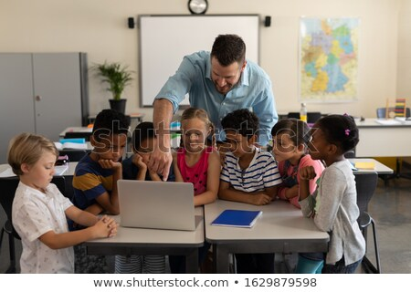 Front view of mixed-race schoolboy showing notebook in a classroom at elementary school Stock photo © wavebreak_media