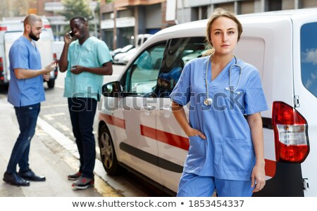 Young female paramedic in uniform hurrying for sick person in ambulance car Stock photo © pressmaster