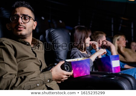 Young man in eyeglasses looking around while taking out camera in cinema Stock photo © pressmaster