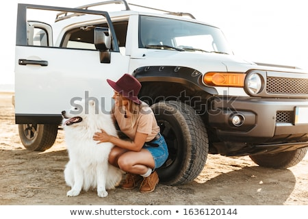 Woman cuddle a dog samoyed outdoors at the beach. Stock photo © deandrobot