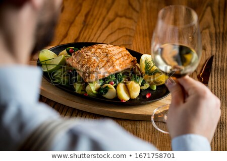Young man eating salmon fillet with gratinated potatoes, leek an Stock photo © boggy
