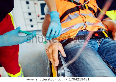 Emergency doctor administering injection needle in ambulance Stock photo © Kzenon
