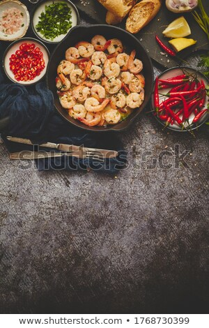 Grilled prawns in cast iron grilling pan with fresh lemon, parsley, chili, garlic white wine sauce Stock photo © dash