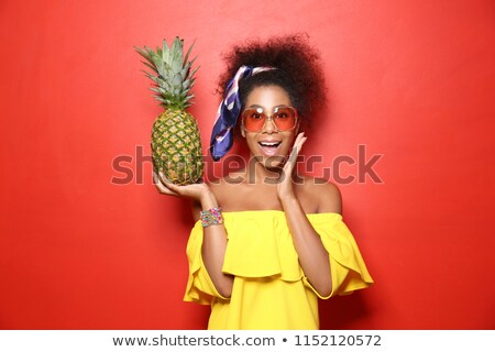 Shocked young african woman holding exotic fruits. Stock photo © deandrobot