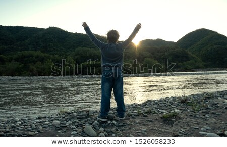 silhouette of child on the beach holding his hands up towards the sun stock photo © zurijeta