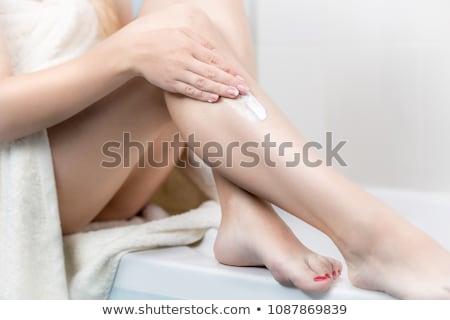 Pretty young woman using body milk. Stock photo © lithian