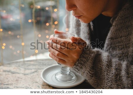 young woman blowing to hot cappuccino coffee sitting at a table Stock photo © Rob_Stark