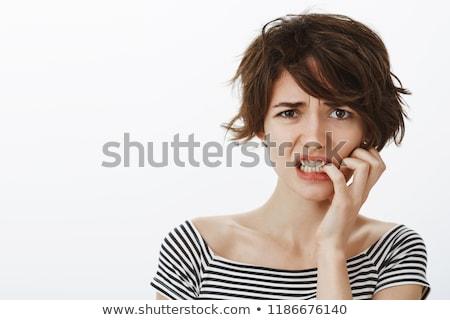 Beautiful young woman biting fingernails Stock photo © bmonteny