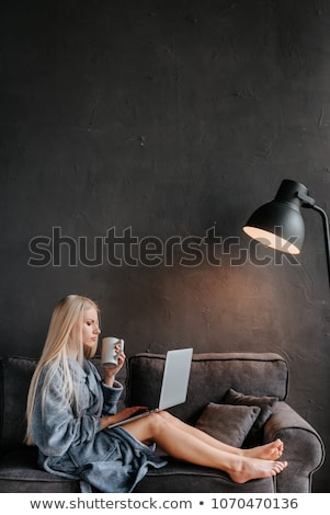 pretty sexy blond woman sitting on couch stock photo © dash