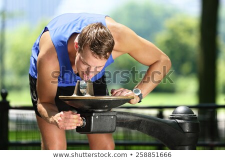 Sport man drinking water from public park fountain Stock photo © Maridav