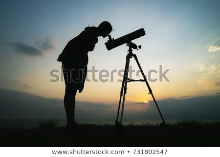 Silhouette of Woman Looking Through Telescope Stock photo © HdcPhoto