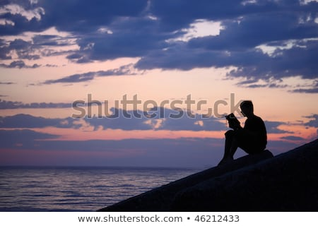 Stock photo: Silhouette guy sitting on breakwater in evening near sea