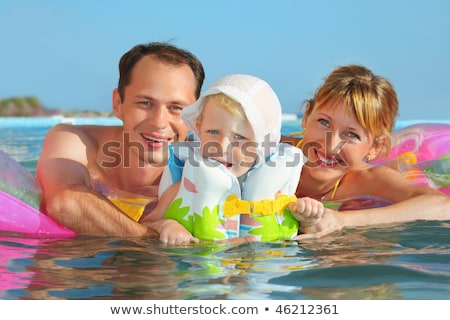Stock photo: Happy family with little girl in white hat and lifejacket bathin