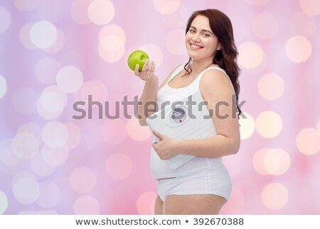 happy plus size woman in underwear with apple stock photo © dolgachov