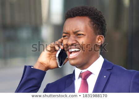 Mad irritated young businessman talking and shouting on cell phone Stock photo © deandrobot