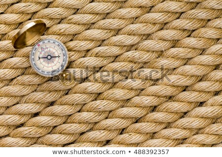 Small magnetic compass on diagonal strands of rope Stock photo © ozgur