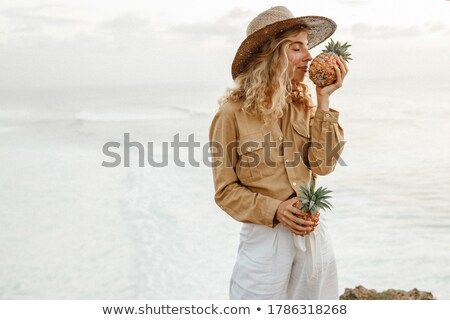 Smiling young lady holding and smells pineapple. Stock photo © deandrobot