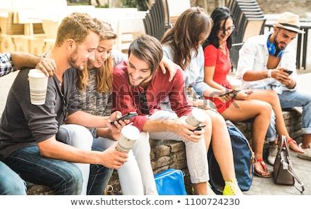 multiethnic friends students using mobile phones stock photo © deandrobot