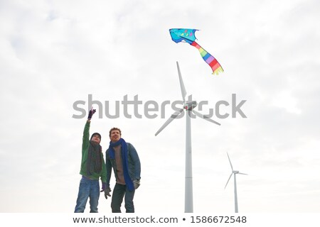 Two Boys Flying Kite at Wind Turbines Stock photo © IS2