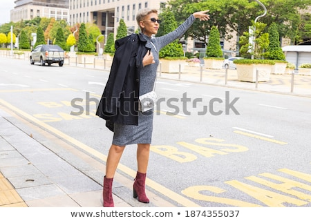 Blonde woman with ladies handbag waving hand stock photo © studioworkstock