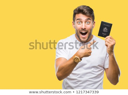 Portrait of a cheerful excited man holding passport stock photo © deandrobot