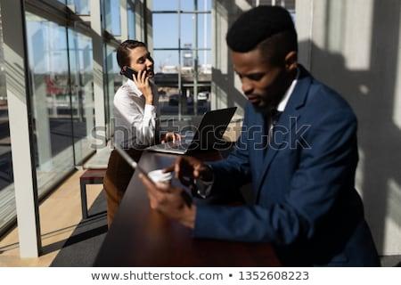 üzletasszony · laptop · beszél · mobiltelefon · boldog · telefon - stock fotó © wavebreak_media