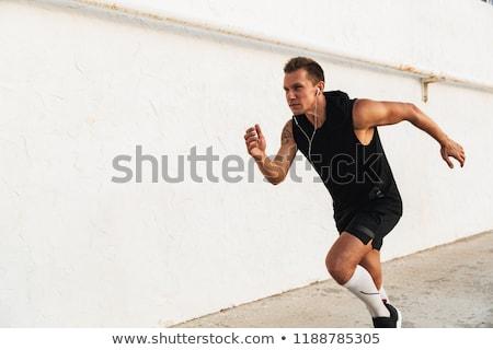 Hátulnézet fiatal sportoló fut tengerpart fejhallgató Stock fotó © deandrobot