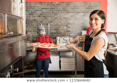 peel placing pizza into oven at pizzeria Stock photo © dolgachov