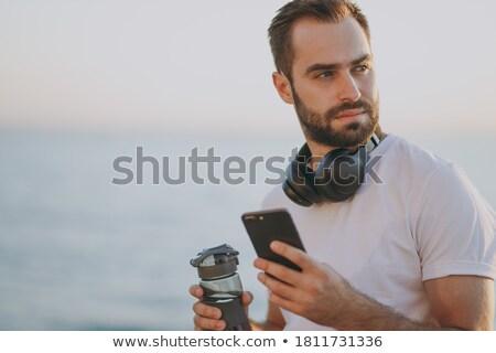 mosolyog · férfi · telefon · part · iroda · munka - stock fotó © dolgachov