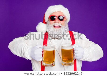 Old man in a Christmas cap with a mug of foam beer Stock photo © rogistok