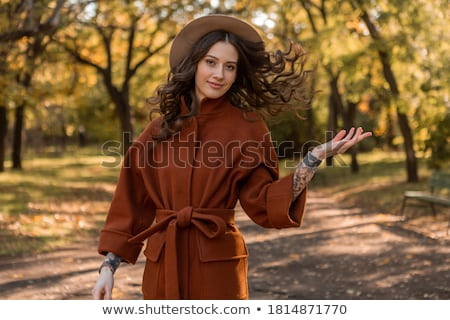Cheerful young woman dressed in autumn coat Stock photo © deandrobot