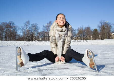 skating woman sitting on the ice smiling. Stock photo © Lopolo