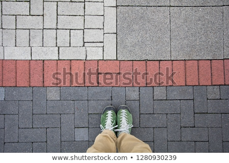 Photo stock: Top View Of A Man Standing On The Colorful Geometrical Pavement
