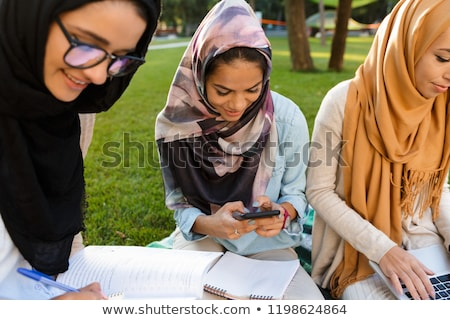 Arabian women students using mobile phone in park outdoors. Stock photo © deandrobot