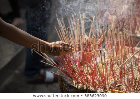 incense sticks on joss stick pot are burning and smoke use for pay respect to the buddha respect to stock photo © galitskaya