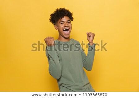 Portrait of happy african man having stylish afro hairdo clenchi Stock photo © deandrobot
