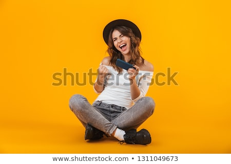 Portrait of caucasian woman wearing hat speaking on smartphone,  Stock photo © deandrobot