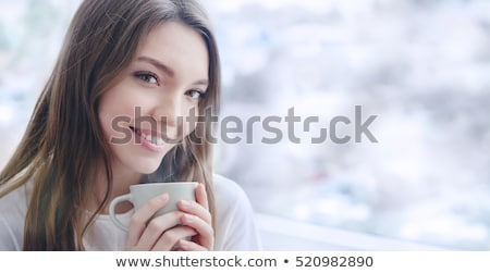 Beautiful smiling young woman with natural make up and long eyelashes holds a cup with hot coffee or Stock photo © ElenaBatkova