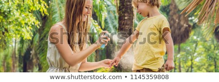 mom and son use mosquito sprayspraying insect repellent on skin outdoor banner long format stock photo © galitskaya