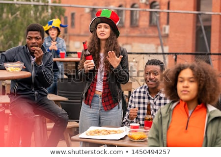 Group of young intercultural fans eating chips and pizza during match broadcast Stock photo © pressmaster