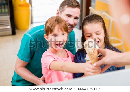 Little girl getting her ice cream cone at the counter of a cafe Stock photo © Kzenon