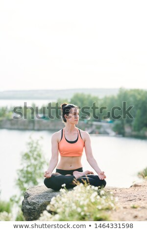 Content female yogis in sports bra sitting in lotus position Stock photo © pressmaster
