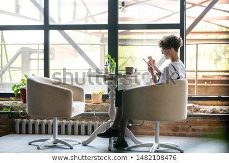 Giovani femminile mobile gadget seduta poltrona Foto d'archivio © pressmaster