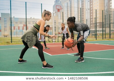 Young African man with ball and blonde sportswoman standing opposite each other Stock photo © pressmaster