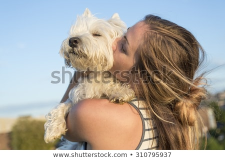 portrait of beautiful girl keeping pretty white West Highland dog outdoor Stock photo © Lopolo