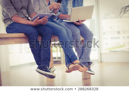 woman showing tablet pc to creative team at office stock photo © dolgachov